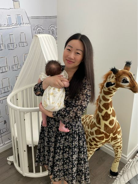 With my baby in her nursery. Her oval shaped mini Stokke crib is so cute and easy to roll from one room to another. The giant giraffe is one I've always wanted growing up so I was thrilled to get it for her nursery. I've linked to the Paris themed wallpaper, which really pulls the whole baby room together.   #LTKhome #LTKbaby