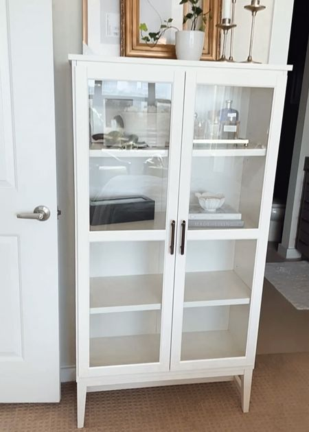 The perfect addition to your small space or apartment bedroom: this glass door book case! Love this affordable find.  Affordable furniture. Budget-friendly home decor. Home Depot. Apartment decor. Apartment furniture. Dresser alternative.   #LTKhome