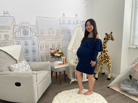 Loved wearing this off shoulder maternity dress, it's so flattering on baby bumps. Here I am in my nursery just a few days before my baby made her grand appearance. It was such a joy to set up the baby room and pick out all the items. I love the Parisian wallpaper, the oval shaped Stokke mini crib, giant giraffe, and super comfortable lounger.   #LTKbump #LTKbaby #LTKhome