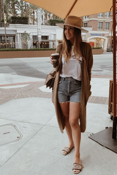 Casual daytime outfit  Graphic t-shirt size small  High waisted Jean shorts agolde size 25 (size ONE down) color epic Duster jacket size small  Summer hat  Summer outfit     #LTKtravel #LTKstyletip #LTKSeasonal