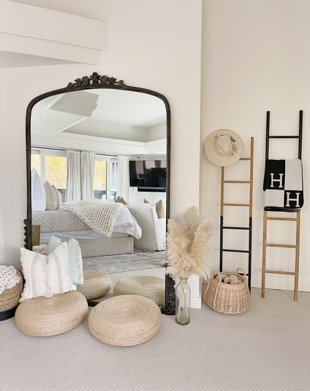 H O M E \ How-to style a bedroom corner! An oversized mirror paired with a set of two-toned blanket ladders, baskets, dried pampas, wicker floor poufs and cozy touches👌🏻   #bedroom #floormirror #mirror #blanketladder #homedecor #masterbedroom #bedroomdecor  #LTKhome #LTKunder100