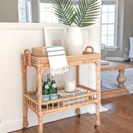"""This side cart is one of my favorite pieces in my home - so fun to decorate for each season, and to use as a bar cart while entertaining! Right now it's 20% off with code """"NEWSEASON"""".  - coastal decor, beach house decor, beach decor, beach style, coastal home, coastal home decor, coastal decorating, coastal interiors, coastal house decor, home accessories decor, coastal accessories, beach style, blue and white home, blue and white decor, neutral home decor, neutral home, natural home decor, serena and lily, serena & lily sale,  rattan bar cart, south seas side cart, coastal decor, beach house decor, beach decor, beach style, coastal home, coastal home decor, coastal modern, coastal interiors, coastal decorating, coastal house decor, coastal farmhouse decor, neutral home decor, coastal living room, neutral living room, living room decor, coastal kitchen, coastal kitchen decor, blue and white home, blue and white decor, cane, seagrass, rattan, coastal modern living room, rattan table, sunroom decor, decor for sunroom, furniture for sunroom, sunroom furniture, bar cart decor, bar cart styling, coastal bar cart, bar cart decorations, turkish towels, turkish hand towels, turkish kitchen towel, turkish towel bathroom, turkish tea towel, turkish towel bath, hand towels bathroom, hand towels kitchen, hand towels white, hand towels for bathroom, hand towel with fringe, striped towels kitchen, white pitcher, white vase large, white vase tall, white vases decorative, white vase with palms, palm leaf, palm leaves, palm leaf stems, palm stems, stems in vase, stems home decor, coffee table decor, decorative bowls wood, decorative bowl decor, decorative bowl coffee table, decorative bowl entryway, decorative bowl dining table, decorative bowl centerpiece, beach print, white frame, white picture frame, serena and lily, serena & lily, west elm, Target home, Target finds, Target decor, Target home decor, Amazon home  #LTKsalealert #LTKstyletip #LTKhome"""