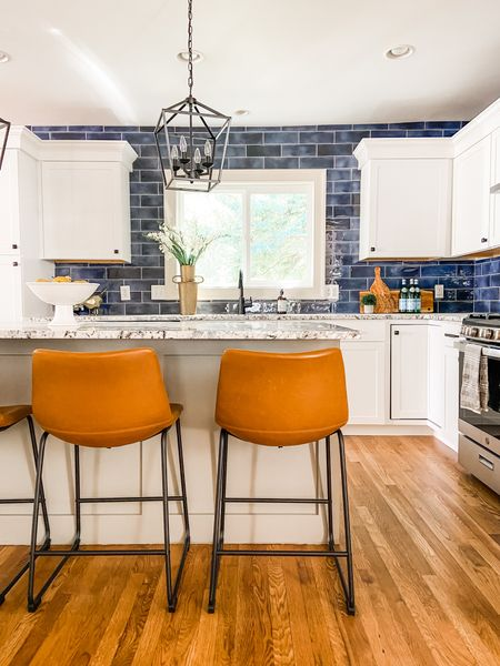 Leather counter stools really pop against the blue backsplash and white cabinets in the kitchen.  Counter stools, leather stools, pendant lighting, lantern light, kitchen decor, kitchen ideas, blue tile  #LTKhome