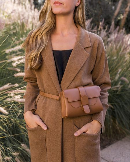 Belt Bag, Long Cardigan, Senreve, Fall Fashion, Silk Cami, Silk Camisole, Coatigan, Sweater Blazer, Dior Lip Gloss  🍂 This leather belt bag is one of my top purchases so far this fall, and it comes in over a dozen colors on Senreve.com. Satin cami is by Vince—similar, less expensive linked. My cardigan coat is my number one recommendation for summer to fall! Light enough for mild weather and warm enough for the A/C and brisk evenings. Runs large.  #satincamisole #blackcami #blackcamisole #tancardigan #cardigancoat #brownleatherbag #cardiganwithpockets #fallpurse #collaredcardigan #camelcoatigan #fallhandbag #fallbag #brownbeltbag #blacksatincami