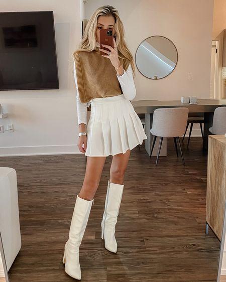 Pleated skirt and white boots http://liketk.it/39sow #liketkit @liketoknow.it #LTKstyletip #LTKshoecrush #LTKSeasonal