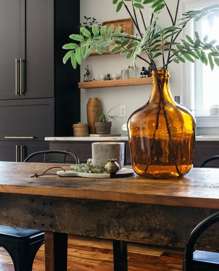 This amber glass vase (demijohn?) is so beautiful in my kitchen with my black cabinets on my rustic vintage wood table. Do you have floating shelves in your kitch? They're so fun to style.  #LTKhome