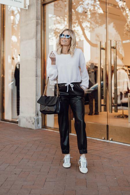 Black faux leather joggers and a white sweatshirt with golden goose sneakers ✔️  #LTKSeasonal #LTKsalealert #LTKunder100