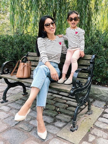 """Classic striped tee & one of my favorite straight leg jeans!  // Super soft Hanna A pima cotton tee on sale with free shipping. unfortunately in kids sizing only (I bought kids 12 for myself which fits like women's XS) and Nori is in 3T. She loves this tee so much I bought her another one in a bigger size for next year! //  Jeans are topshop straight in """"bleach"""" wash size 25 regular which is very petite friendly in length and fit (I go up 1 size at the waist from my usual in other brands). These same jeans also come in Petite (linked) but the regular length fit short enough on me //  Bag is polene Paris # 8 mini (not linkable) // Shoes are rothys ecru 5.5 but I found a few other more affordable sustainable flat shoes alternatives that look great!!  //  Sunglasses are old Thierry lasry brand from shopbop but I linked similar from jcrew. Nori's are Janie and jack.   #LTKsalealert #LTKSeasonal #LTKfamily"""