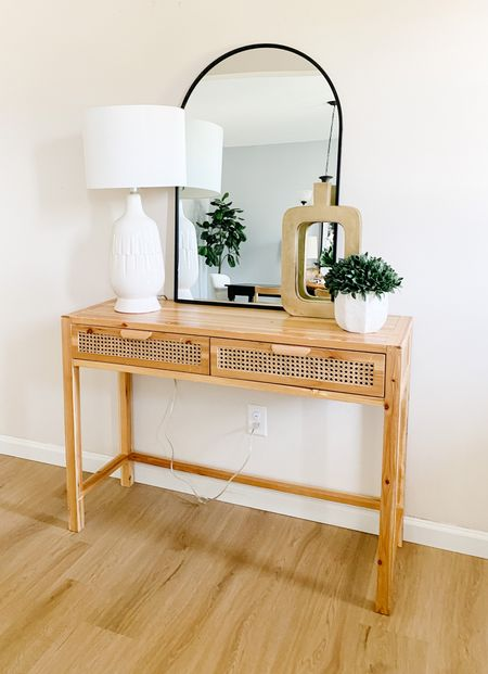 The black arched mirror pops against the wicker console table.  Console style, entry way table, arched mirrors, vignette styling, gold vase, home decor  #LTKhome