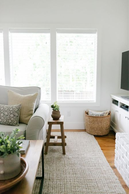 Living room decor. Loving this corner with a cute stool as a side table and the basket filled with pillows.    #LTKstyletip #LTKunder100 #LTKhome
