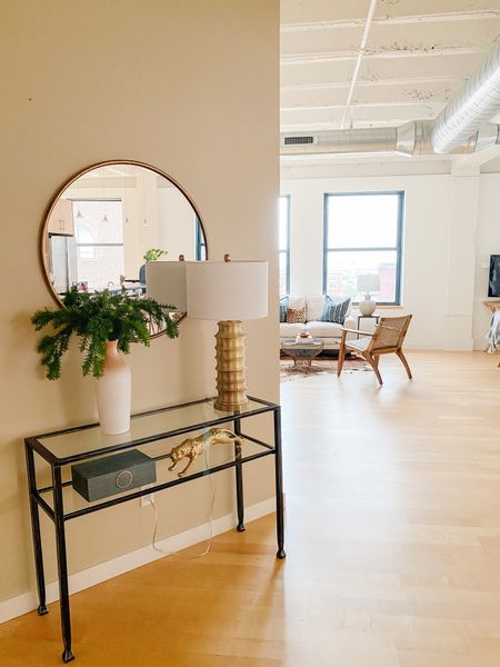 Love this round gold mirror over the black console table in a loft entry.  Console table, entry decor, loft decor, round mirror, console style, home decor, gold lamp  #LTKhome